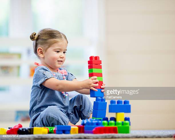 Little Girl Building Lego Towers