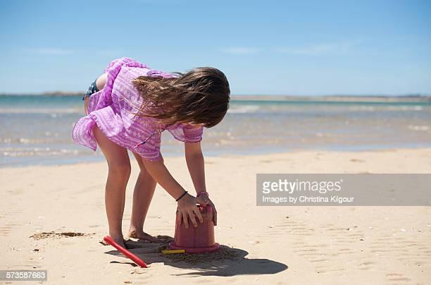 Little girl building sandcastles