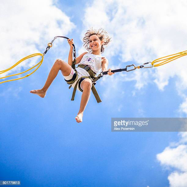 Little girl bungee jumping at trampoline