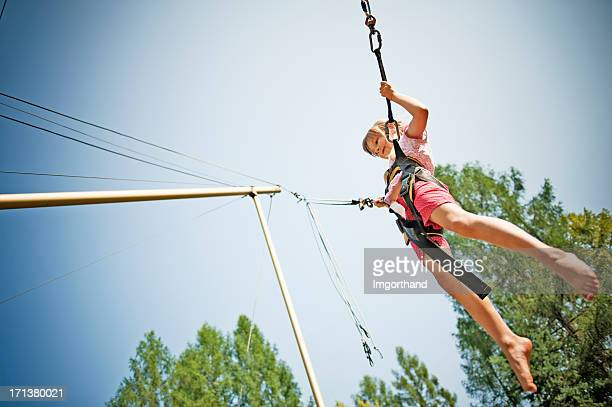 Little girl bungee jumping on trampoline