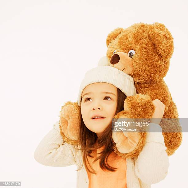 A Little Girl Carrying Teddy Bear On Shoulder