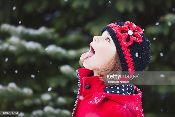 Little girl catching snowflakes on her tongue