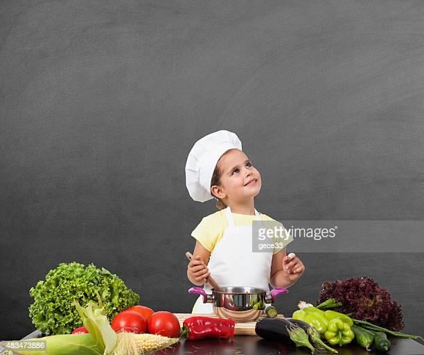 Little Girl Chef Thinking of  on Blackboard