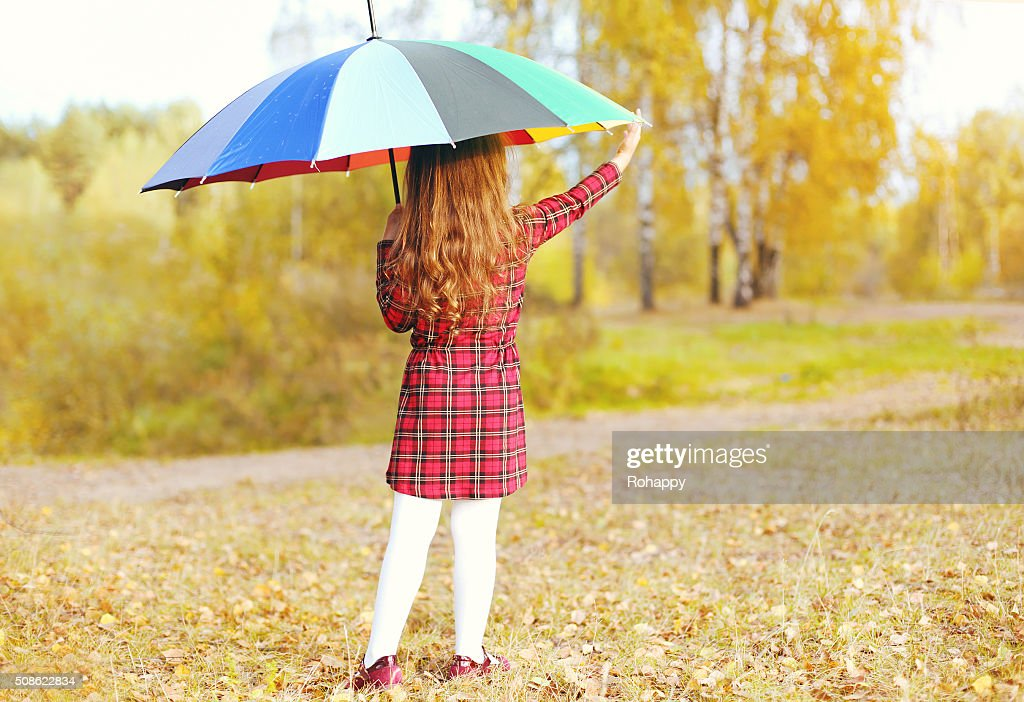 Little girl child with colorful umbrella in autumn day : Stock Photo