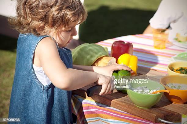 Little girl choping bell pepper on table in the garden