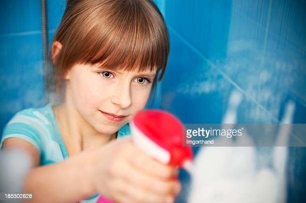 Little girl cleaning a shower window