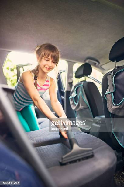 Little girl cleaning car interior