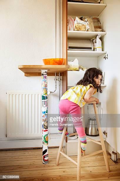 little girl climbing a kitchen chair