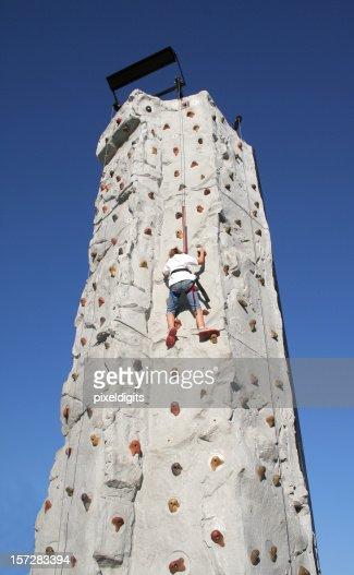 Little Girl Climbing A Tall Wall