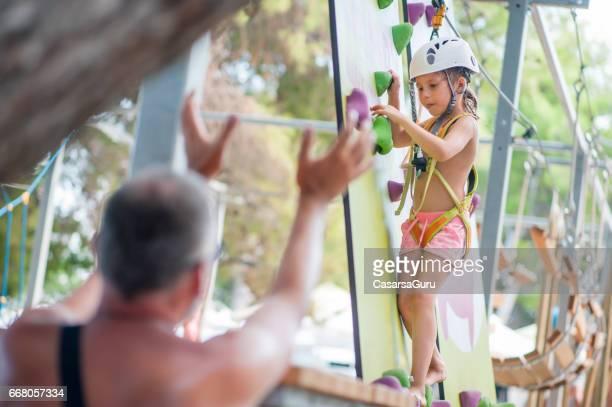 Petite fille d'escalade dans le parc d'aventure