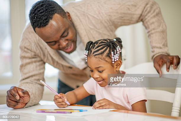 Little Girl Coloring a Picture with Her Father