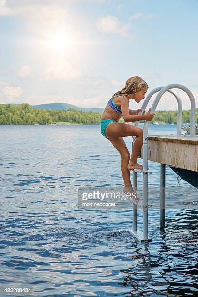 Little girl coming out of lake climbing on pier ladder.