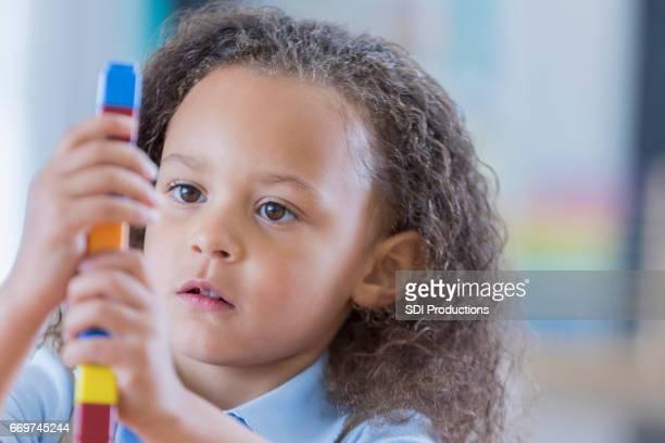 Kleines Mädchen konzentriert sich während des Spiels mit Würfel zählen