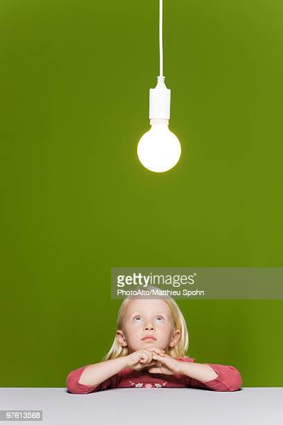 Little girl contemplating illuminated light bulb suspended overhead