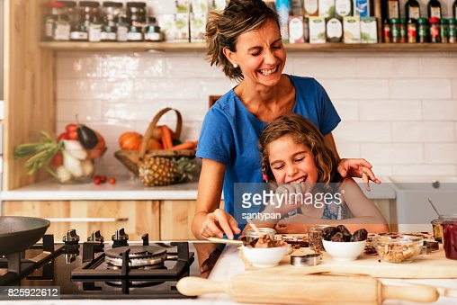 Little girl cooking with her mother in the kitchen. : Stock Photo