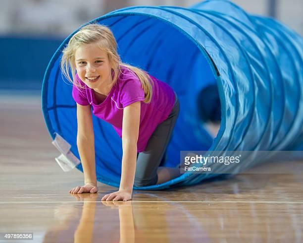 Little Girl Crawling Through a Tunnel