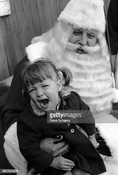 A little girl cries as she sits on the lap of an unidentified man in a Santa Claus costume Albion New York 1964