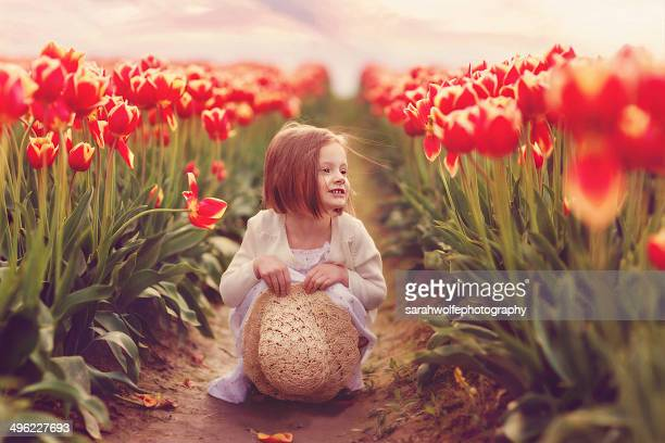 little girl crouching in a tulip field