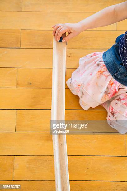 Little girl crouching on floor playing with marble run
