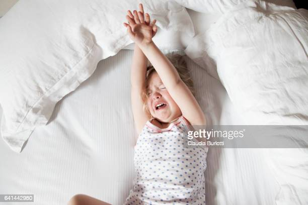 Little girl crying in bed
