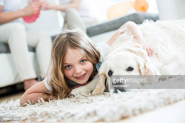 Little girl cuddling with her dog, lying on floor, parents in background