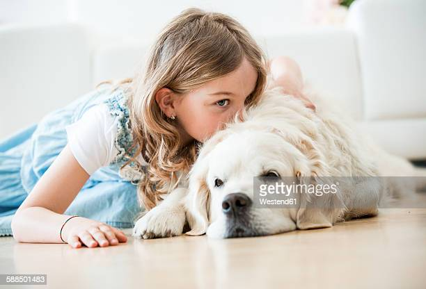 Little girl cuddling with her dog, lying on floor