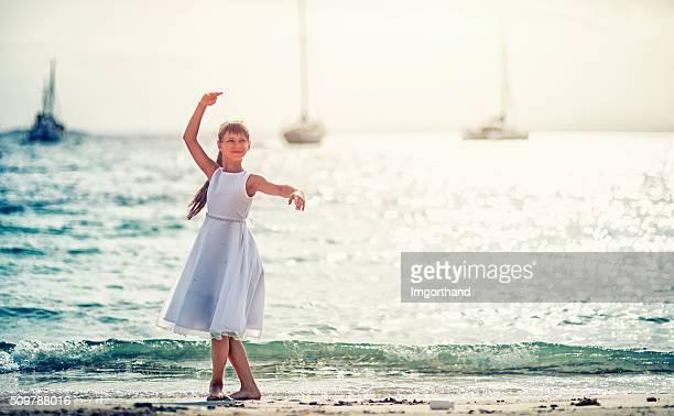 Little girl dancing ballet on the beach