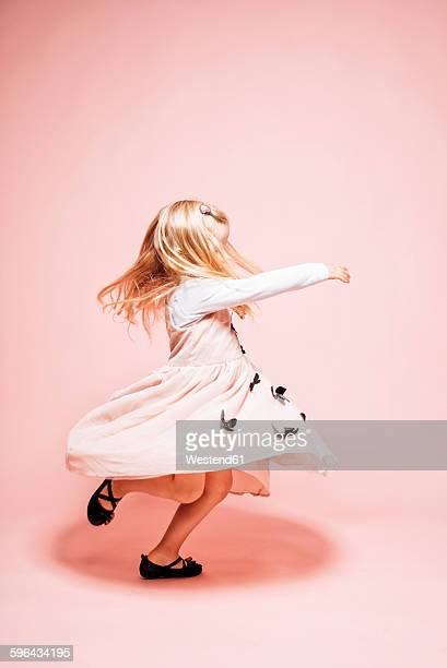 Little girl dancing in front of pink background