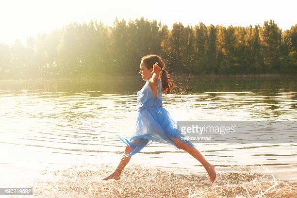 Little girl dancing in lake water.