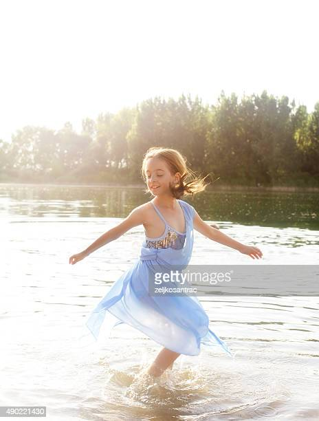 Little girl dancing in lake water.