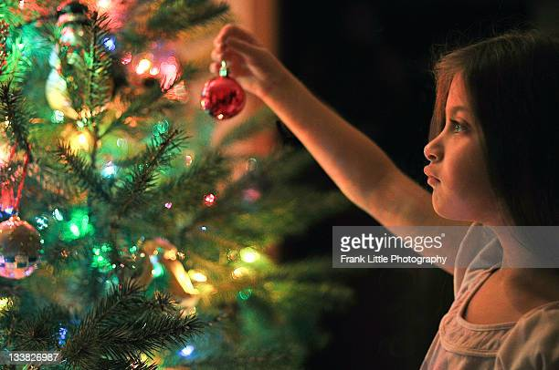 Little girl decorating beautiful Christmas tree