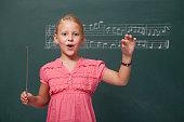 Little Girl Directing Chorus For Folk Music Before Blackboard