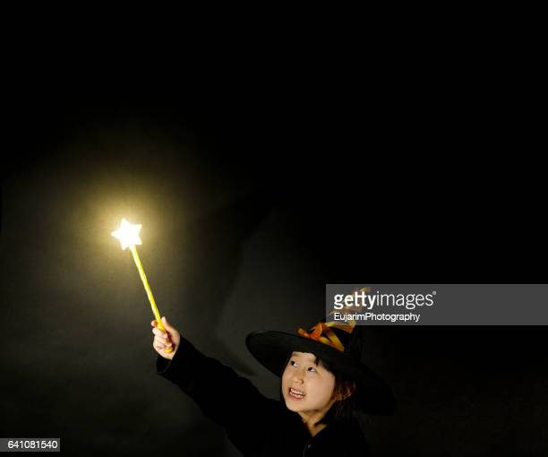 Little girl disguised as wizard, holding shining star shaped magic wand