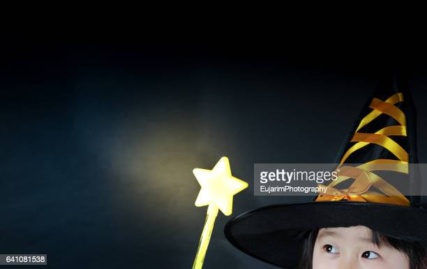 Little girl disguised as wizard, holding star shaped magic wand