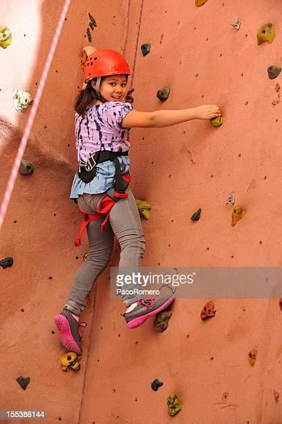 Little girl doing rock climbing indoors