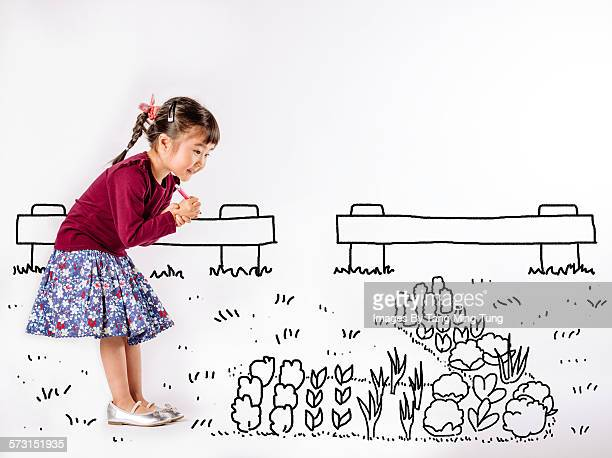 Little girl drawing a garden on white background