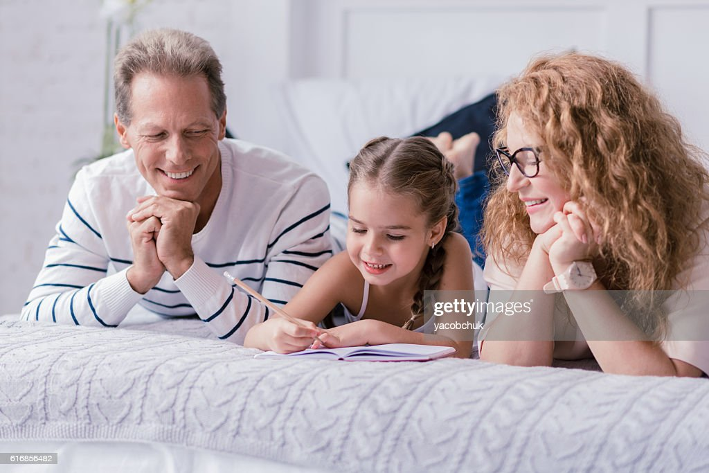 Little girl drawing and having fun with her grandparents : Stock Photo