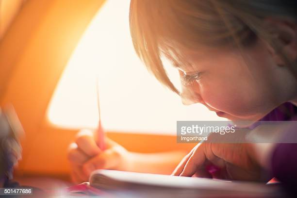 Little girl drawing by the window