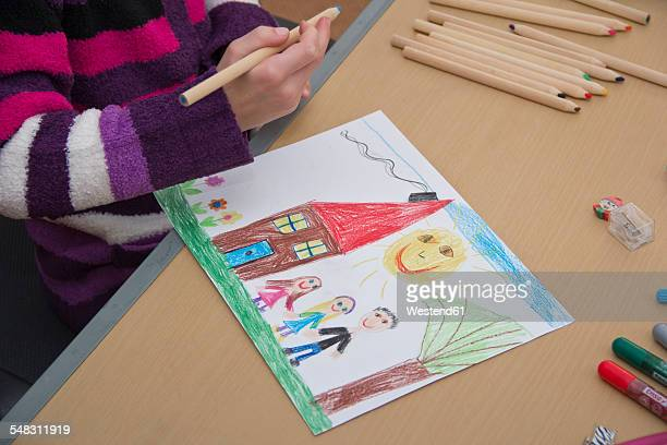 Little girl drawing happy family