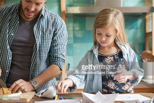 Little girl drawing in kitchen while family prepares meal