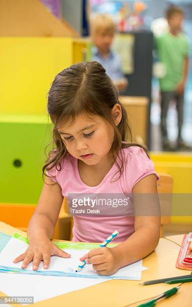 Little Girl Drawing In Library