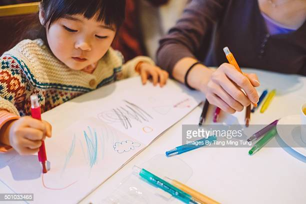 Little girl drawing with mom in restaurant