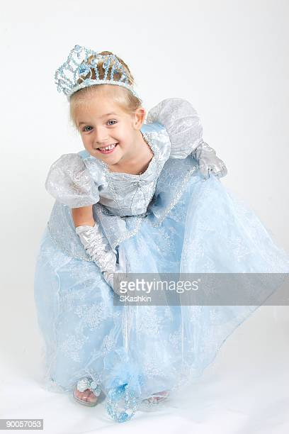 A little girl dressed as a princess bowing and smiling