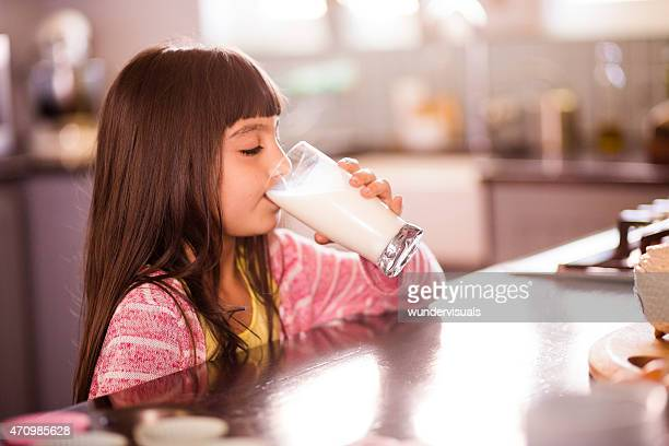 Little girl drinking a glass of milk in her kitchen