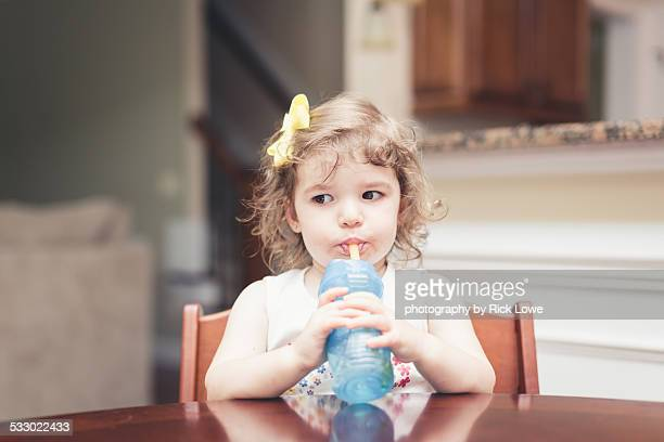 Little girl drinking from a straw