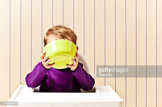 Kleines Mädchen trinken aus Frühstücksschale