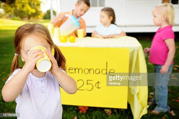 Petite fille buvant Limonade devant un Stand