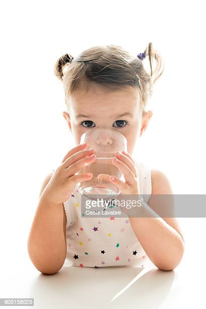 Little girl drinking water from glass