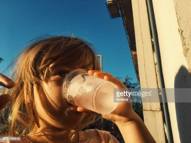 Little girl drinking water from plastic cup during hot summer day