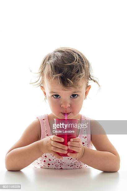 Little girl drinking with a straw